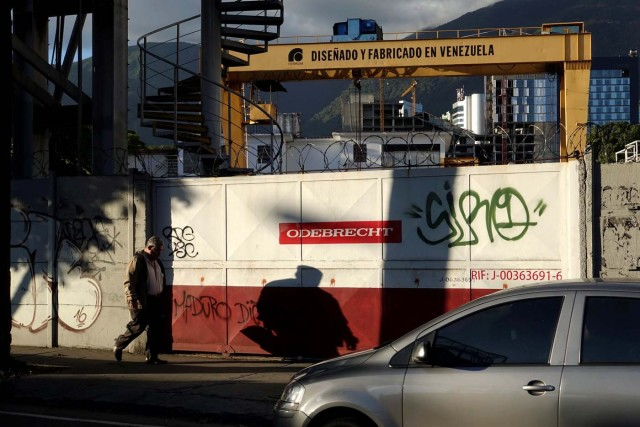 """A man walks past corporate logo of Odebrecht in a construction site with a text in a structure that reads """"Designed and made in venezuela"""" in Caracas"""