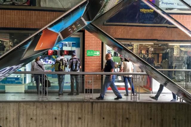 ACOMPAÑA CRÓNICA: VENEZUELA DIVISAS - CAR01. CARACAS (VENEZUELA), 27/01/2017.- Fotografía del 25 de febrero del 2017, donde se observa a unas personas ver una vitrina en un centro comercial en la ciudad de Caracas (Venezuela). En una vitrina de una tienda caraqueña se exhibe un móvil de última generación a un precio de 1.280.000 bolívares, una cantidad que puede pagarse con dólares estadounidenses en este lugar y en otros que operan con varias divisas pese al control de cambio que rige en Venezuela desde 2003. EFE/MIGUEL GUTIÉRREZ