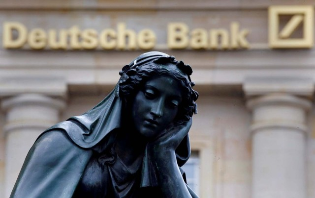 FILE PHOTO - A statue is seen next to the logo of Germany's Deutsche Bank in Frankfurt, Germany, January 26, 2016. REUTERS/Kai Pfaffenbach/File Photo
