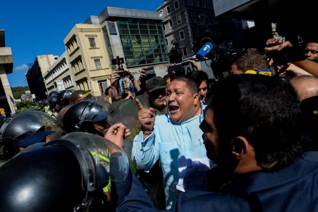 Venezuela's National Guard personnel prevent opposition deputy Jose Brito from entering the National Electoral Council (CNE) in Caracas on January 2, 2017. A group of opposition lawmakers had their way blocked by police when they tried to get into the CNE to demand the organism to call for regional elections that were due to happen last year. A group of opposition lawmakers had their way blocked by police when they tried to get into the CNE to demand the organism to call for regional elections that were due to happen last year. / AFP PHOTO / FEDERICO PARRA