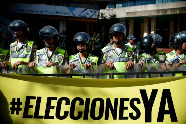 "Riot police stand behind a banner that reads ""Elections now"" in fornt the National Electoral Council (CNE) in Caracas on January 2, 2017. A group of opposition lawmakers had their way blocked by police when they tried to get into the CNE to demand the organism to call for regional elections that were due to happen last year. / AFP PHOTO / FEDERICO PARRA"