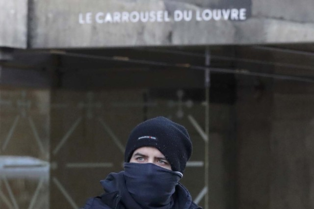 A masked French policeman is seen in front of the street entrance of the Carrousel du Louvre in Paris, France, February 3, 2017 after a French soldier shot and wounded a man armed with a machete and carrying two bags on his back as he tried to enter the Paris Louvre museum. REUTERS/Christian Hartmann
