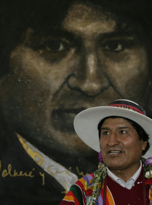 Bolivia's President Evo Morales poses in front of a painting of himself after the inauguration of the Orinoca Museum in Orinoca