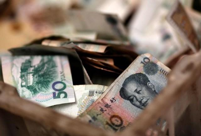 En la imagen, billetes chinos en la caja de cambio de un vendedor en un mercado de Pekín (Foto REUTERS/Kim Kyung-Hoon)