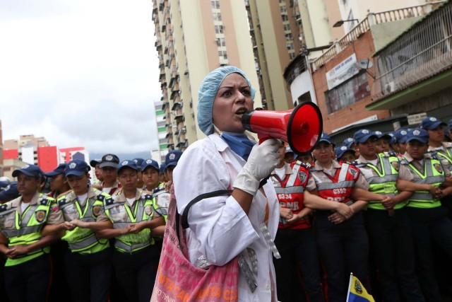 A woman shouts slogans in front of the riot police during a rally of workers of the health sector and opposition supporters, due to the shortages of basic medical supplies and against Venezuelan President Nicolas Maduro's government in Caracas, Venezuela February 7, 2017. REUTERS/Carlos Garcia Rawlins