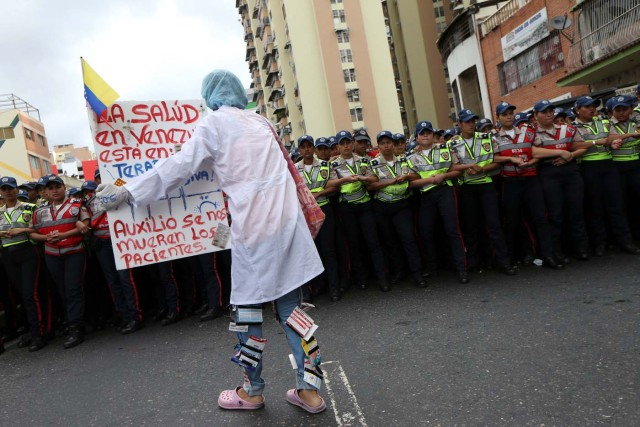 "A woman holds a placard in front of the riot polices during a rally of workers of the health sector and opposition supporters, due to the shortages of basic medical supplies and against Venezuelan President Nicolas Maduro's government in Caracas, Venezuela February 7, 2017. The placard reads, ""Help us, the patients are dying"". REUTERS/Carlos Garcia Rawlins"