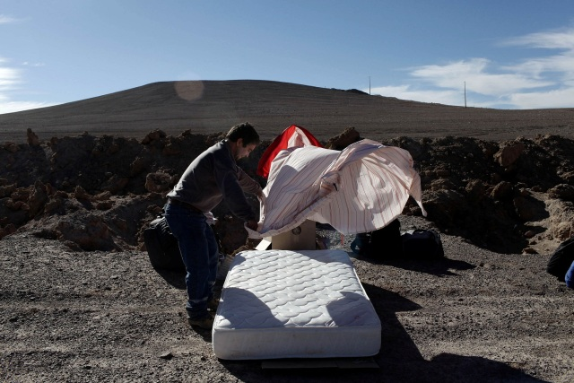 A worker from Escondida, the world's biggest copper mine, makes the bed as they prepare to camp outside the company gates during a strike, in Antofagasta, Chile February 9, 2017. REUTERS/Juan Ricardo EDITORIAL USE ONLY. NO RESALES. NO ARCHIVE