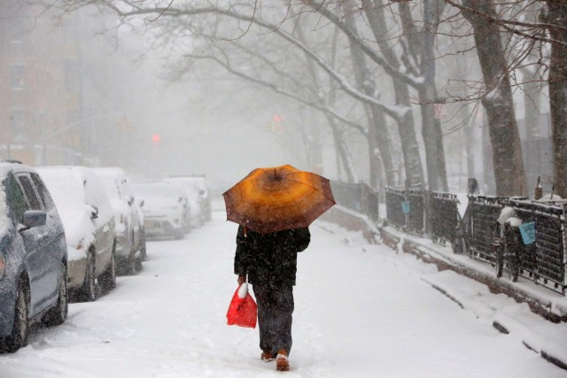 A man walks through the Lower East Side as snow falls in Manhattan, New York, U.S. February 9, 2017. REUTERS/Andrew Kelly