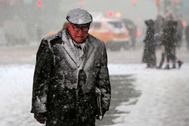 A man walks in Times Square as snow falls in Manhattan, New York, U.S. February 9, 2017. REUTERS/Andrew Kelly