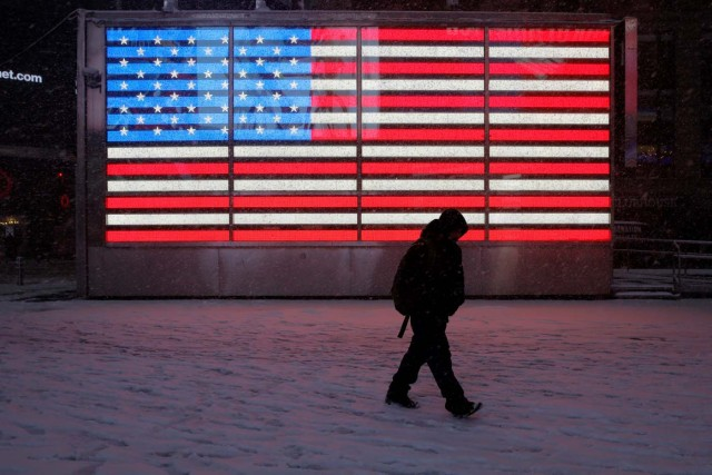 A person walks in Times Square as snow falls in Manhattan, New York, U.S. February 9, 2017. REUTERS/Andrew Kelly