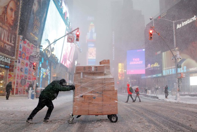 A man attempts to deliver packages in Times Square as heavy snow falls in Manhattan, New York, U.S. February 9, 2017. REUTERS/Andrew Kelly