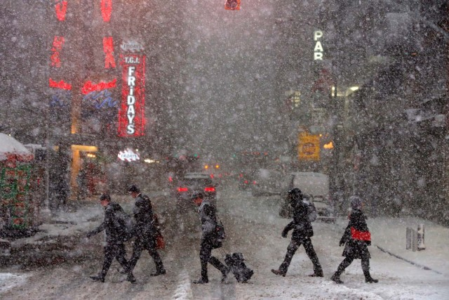 Pedestrians walk in Times Square as snow falls in Manhattan, New York, U.S. February 9, 2017. REUTERS/Andrew Kelly