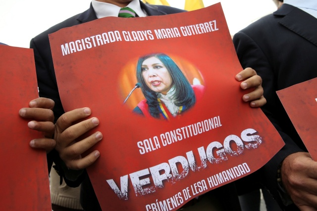 Juan Matheus, deputy of the opposition party Justice First (Primero Justicia) holds a placard with an image of Venezuela's Supreme Court President Gladys Gutierrez during a protest against Venezuelan President Nicolas Maduro's government outside the Supreme Court of Justice (TSJ) in Caracas, Venezuela February 9, 2017. REUTERS/Carlos Garcia Rawlins