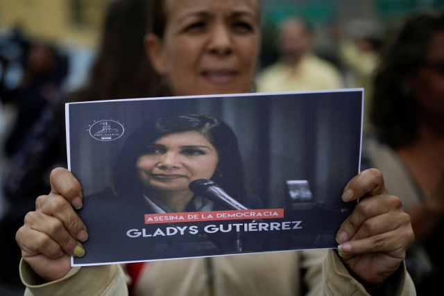 """An opposition supporter holds a placard with an image of Venezuela's Supreme Court President Gladys Gutierrez that reads """"Murderer of democracy"""", during a protest against Venezuelan President Nicolas Maduro's government outside the Supreme Court of Justice (TSJ) in Caracas, Venezuela February 9, 2017. REUTERS/Marco Bello"""