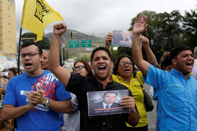 Opposition supporters holding images of judges shout slogans during a protest against Venezuelan President Nicolas Maduro's government outside the Supreme Court of Justice (TSJ) in Caracas, Venezuela February 9, 2017. REUTERS/Marco Bello