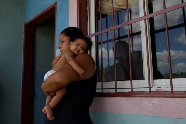 Jennifer Vivas, mother of Eliannys Vivas, who died from diphtheria, carries her baby at the front porch of her home in Pariaguan, Venezuela January 26, 2017. Picture taken January 26, 2017. REUTERS/Marco Bello