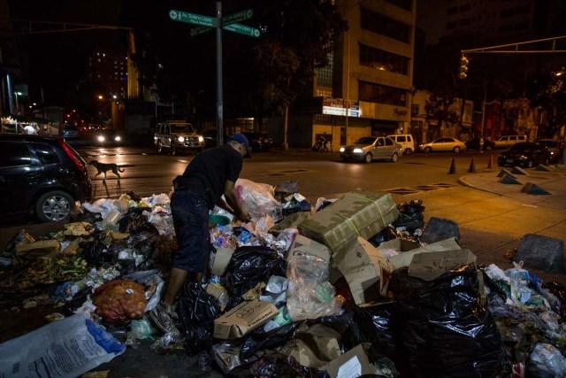 ACOMPAÑA CRÓNICA: VENEZUELA CRISIS. CAR12. CARACAS (VENEZUELA), 31/12/2016.- Varias personas buscan comida entre bolsas de basura este jueves, 31 de diciembre de 2016, en Caracas (Venezuela). La profunda crisis que aqueja a Venezuela trajo como consecuencia escasez y hambre, lo que a su vez ha llevado a familias enteras a buscar restos de alimentos en los basureros y, muchas veces, a pelear con otras personas sin recursos, por un desecho comestible o algún material reciclable que se pueda vender. EFE/Miguel Gutiérrez