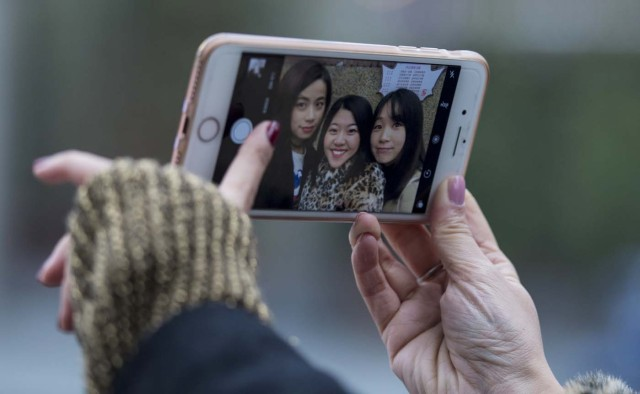 """This picture taken on January 8, 2017 shows (from L-R) Peng Lin, Wang Peng and Hu Dongyuan posing for a selfie in the streets of Shanghai. Strolling a tree-lined Shanghai street with friends, Hu Dongyuan pulls out her smartphone and does what millions of Chinese women do daily: take a selfie, digitally """"beautify"""" their faces, and pop it on social media. Such virtual makeovers, typically involving lightening skin, smoothing out complexions and rounding the eyes, have propelled selfie-editing app Meitu to the top ranks of China downloads. / AFP PHOTO / Johannes EISELE / TO GO WITH China-technology-lifestyle-apps-selfies-Meitu, FEATURE by Albee ZHANG"""