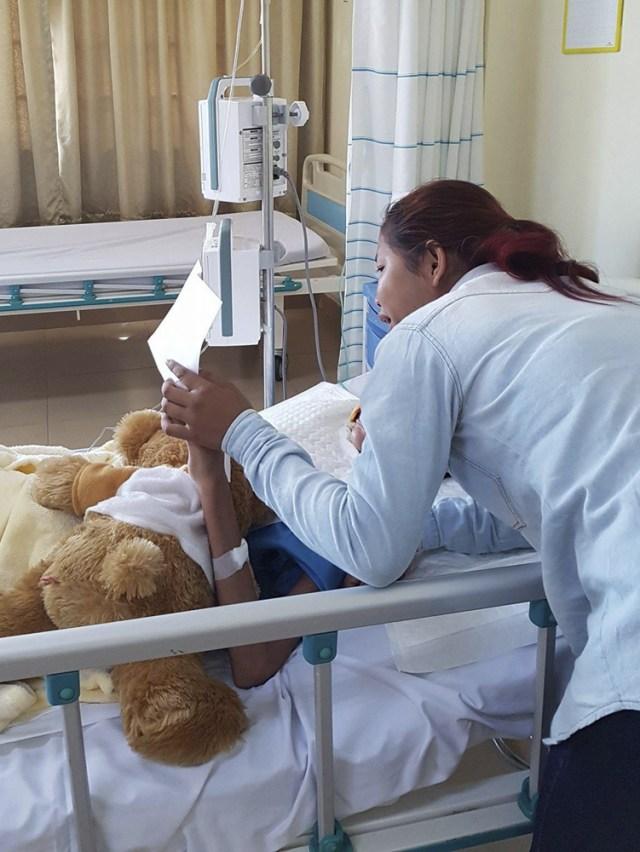 GRA045. PHNOM PENH, 09/03/2017.- Fotografía facilitada por Yulia Khouri de Soth Rey, que ha perdido gran parte de su rostro a causa de una necrosis, sostiene la mano de su hermana Boh Rey en el hospital privado Sen Sok International, en Phnom Penh. Dos hospitales públicos camboyanos rechazaron atender a Soth Rey, cuando vieron la gravedad de la enfermedad y que su familia carecía de medios para pagar por adelantado. Sin ayuda médica, los familiares de Soth Srey, de 18 años y residente en Siem Riep, perdieron la esperanza para salvar a su hija, quien en diciembre contrajo un catarro o una alergia -los médicos aún no lo han esclarecido-, antes de sufrir una infección en la nariz que degeneró en una necrosis. Hace menos de un mes, el caso llegó a través de las redes sociales a la expatriada Yulia Khouri, residente también de Siem Reap, en el noroeste de Camboya. Las donaciones de Khouri y otras personas anónimas permitieron que Soth Srey haya sido ingresada en el hospital privado Sen Sok International de la capital camboyana, donde llegó el pasado 26 de febrero con 41 grados de fiebre, una neumonía septicémica, deshidratada y con 35 kilogramos de peso debido a la malnutrición. EFE (SOLO USO EDITORIAL)