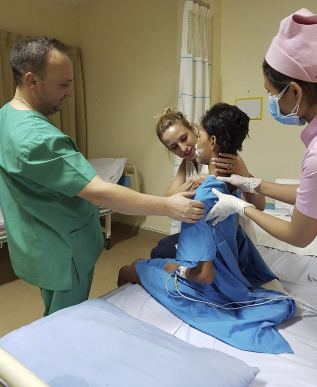 GRA046. PHNOM PENH, 09/03/2017.- Fotografía facilitada por Yulia Khouri (c, detrás) de la joven Soth Rey, que ha perdido gran parte de su rostro a causa de una necrosis, y consigue sentarse después de estar convaleciente durante semanas mientras la sostiene el director ejecutivo del hospital privado Sek Son International, Ivan Matela y una enfermera, en Phnom Penh. Dos hospitales públicos camboyanos rechazaron atender a Soth Rey, cuando vieron la gravedad de la enfermedad y que su familia carecía de medios para pagar por adelantado. Sin ayuda médica, los familiares de Soth Srey, de 18 años y residente en Siem Riep, perdieron la esperanza para salvar a su hija, quien en diciembre contrajo un catarro o una alergia -los médicos aún no lo han esclarecido-, antes de sufrir una infección en la nariz que degeneró en una necrosis. Hace menos de un mes, el caso llegó a través de las redes sociales a la expatriada Yulia Khouri, residente también de Siem Reap, en el noroeste de Camboya. Las donaciones de Khouri y otras personas anónimas permitieron que Soth Srey haya sido ingresada en el hospital privado Sen Sok International de la capital camboyana, donde llegó el pasado 26 de febrero con 41 grados de fiebre, una neumonía septicémica, deshidratada y con 35 kilogramos de peso debido a la malnutrición. EFE (SOLO USO EDITORIAL)