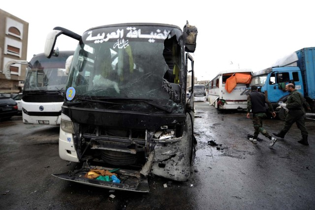 Damaged buses are pictured at the site of an attack by two suicide bombers in Damascus, Syria March 11, 2017. REUTERS/Omar Sanadiki