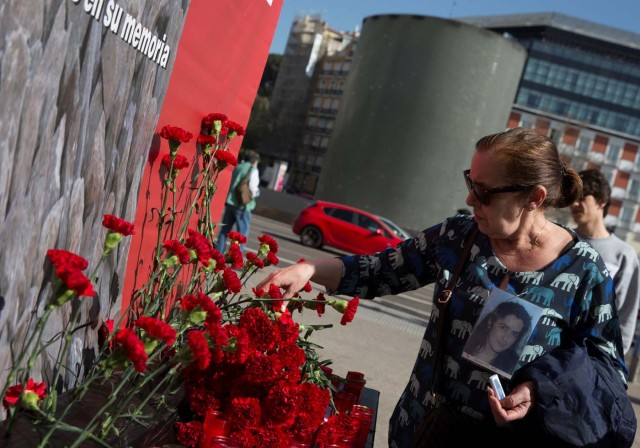 A relative of a victim of the Madrid train attacks places a flower outside Atocha station on the 13th anniversary of the attacks in Madrid, Spain, March 11, 2017. REUTERS/Sergio Perez