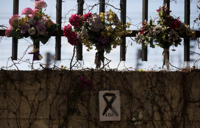 A message with a black ribbon hangs from a wall at the same spot where a train was bombed in the 2004 Madrid train bombings, at a memorial site for the victims of the bombings, near Atocha station in Madrid, Spain, March 11, 2017. REUTERS/Sergio Perez