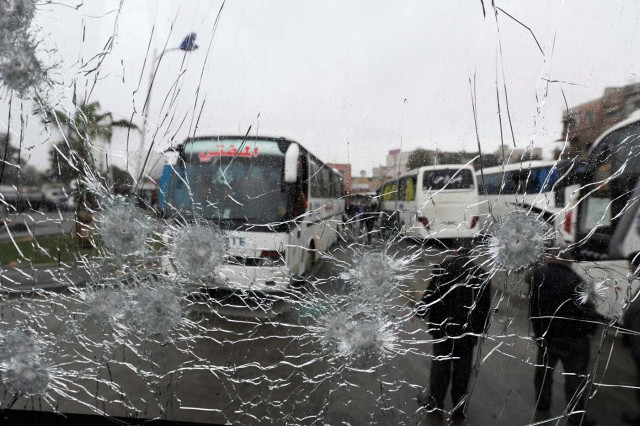 People are seen though a shattered glass window of a bus at the site of an attack by two suicide bombers in Damascus, Syria March 11, 2017. REUTERS/Omar Sanadiki TPX IMAGES OF THE DAY