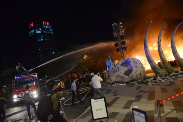"""This picture taken on March 9, 2017 shows firefighter truck injecting water to control a fire on a giant model of King Kong during the premiere of the """"Kong: Skull Island"""" in Ho Chi Minh City. Film buffs with the hottest ticket in town were left running for safety after a giant model of King Kong went up in flames at the sizzling Vietnam premiere of the rebooted horror classic. / AFP PHOTO / STR"""