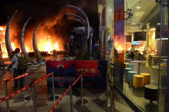 """This picture taken on March 9, 2017 shows photographer taking picture of a fire on a giant model of King Kong during the premiere of the """"Kong: Skull Island"""" in Ho Chi Minh City. Film buffs with the hottest ticket in town were left running for safety after a giant model of King Kong went up in flames at the sizzling Vietnam premiere of the rebooted horror classic. / AFP PHOTO / STR"""