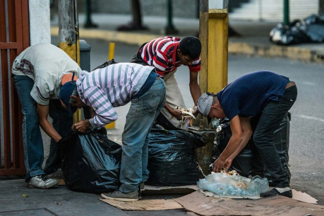 Personas buscan en la basura algopara comer ante la crisis actual en Venezuela. / AFP PHOTO / Federico PARRA
