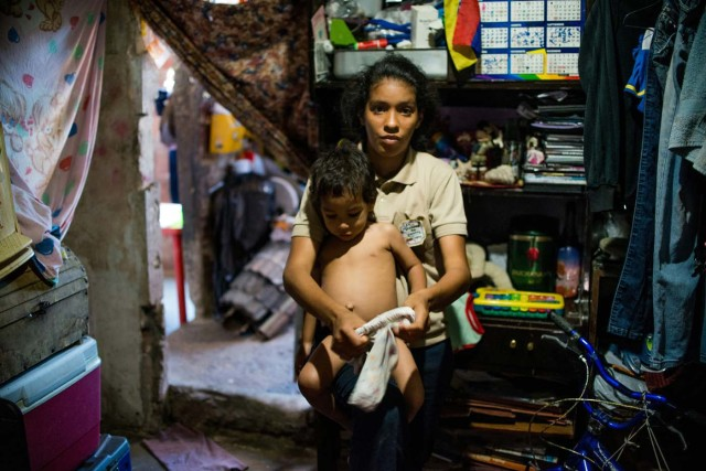 Venezuelan Rebeca Leon, who scavanges for food in the streets of Caracas, poses with her two-year-old son at her house in Petare shantytown, on February 22, 2017. Venezuelan President Nicolas Maduro is resisting opposition efforts to hold a vote on removing him from office. The opposition blames him for an economic crisis that has caused food shortages. / AFP PHOTO / Federico PARRA
