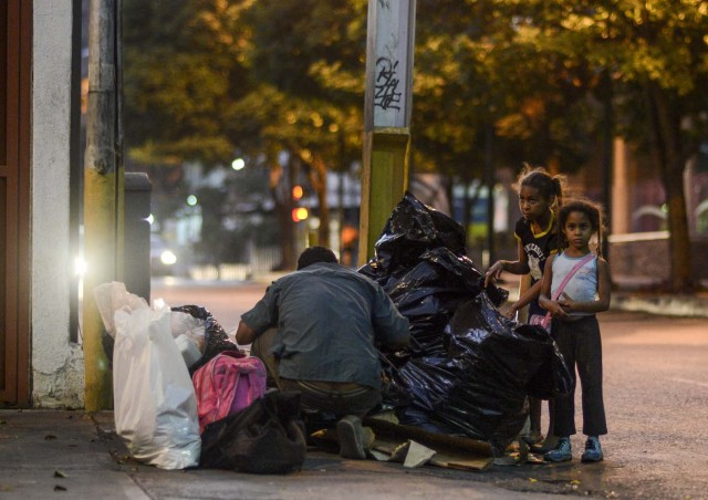 A man scavenges for food next to girls in the streets of Caracas on February 21, 2017. Venezuelan President Nicolas Maduro is resisting opposition efforts to hold a vote on removing him from office. The opposition blames him for an economic crisis that has caused food shortages. / AFP PHOTO / JUAN BARRETO / TO GO WITH AFP STORY BY Alexander Martinez
