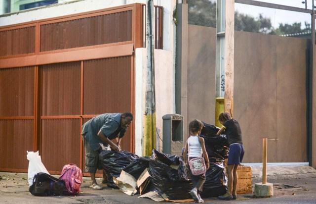 Un hombre y dos niñas escarban en la basura en Caracas AFP PHOTO / JUAN BARRETO