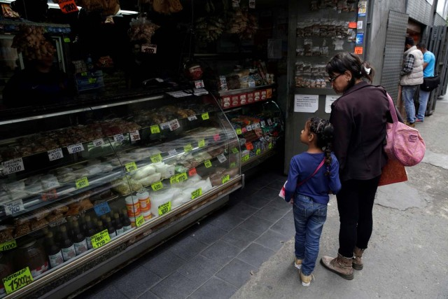 A woman and a child look at prices in a grocery store in downtown Caracas, Venezuela March 10, 2017. REUTERS/Marco Bello