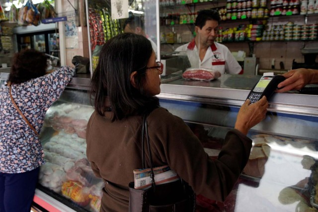 A woman uses a PoS device to pay for her groceries at a store in downtown Caracas, Venezuela March 10, 2017. REUTERS/Marco Bello