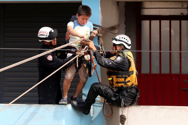 A child gets rescued after a massive landslide and flood in the Huachipa district of Lima, Peru March 17, 2017. REUTERS/Guadalupe Pardo