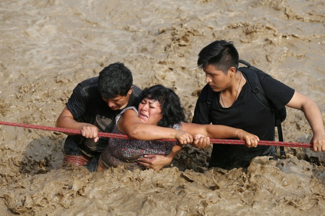 REFILE - CORRECTING NAME OF THE RIVER A woman is assisted while crossing a flooded street after the Huaycoloro river overflooded its banks sending torrents of mud and water rushing through the streets in Huachipa, Peru, March 17, 2017. REUTERS/Guadalupe Pardo TPX IMAGES OF THE DAY