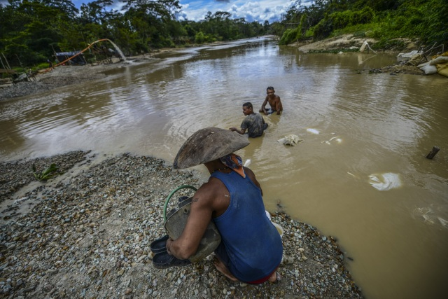 Men work at Nacupay gold mine on the bank of a river in El Callao, Bolivar state, southeastern Venezuela on February 24, 2017. Although life in the mines of eastern Venezuela is hard and dangerous, tens of thousands from all over the country head for the mines daily in overcrowded trucks, pushed by the rise in gold prices and by the severe economic crisis affecting the country, aggravated recently by the drop in oil prices. / AFP PHOTO / JUAN BARRETO