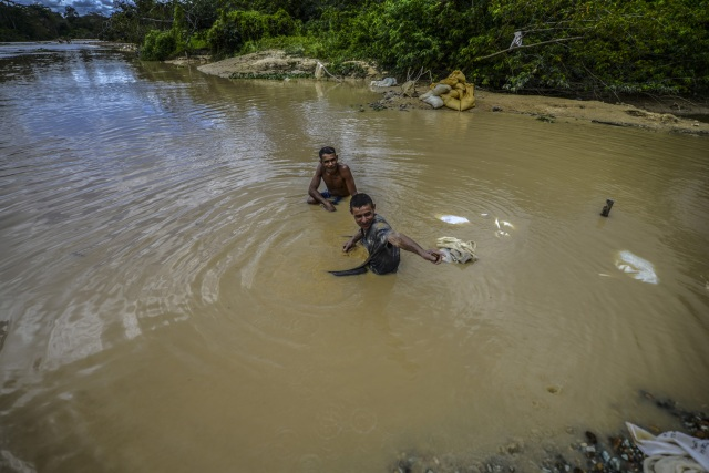 Men work at Nacupay gold mine on the banks of a river in El Callao, Bolivar state, southeastern Venezuela on February 24, 2017. Although life in the mines of eastern Venezuela is hard and dangerous, tens of thousands from all over the country head for the mines daily in overcrowded trucks, pushed by the rise in gold prices and by the severe economic crisis affecting the country, aggravated recently by the drop in oil prices. / AFP PHOTO / JUAN BARRETO / TO GO WITH AFP STORY by Maria Isabel SANCHEZ