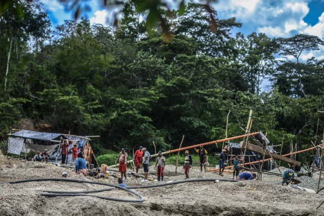 Men work at a gold mine on the banks of a river in El Callao, Bolivar state, southeastern Venezuela on February 24, 2017. Although life in the mines of eastern Venezuela is hard and dangerous, tens of thousands from all over the country head for the mines daily in overcrowded trucks, pushed by the rise in gold prices and by the severe economic crisis affecting the country, aggravated recently by the drop in oil prices. / AFP PHOTO / JUAN BARRETO / TO GO WITH AFP STORY by Maria Isabel SANCHEZ