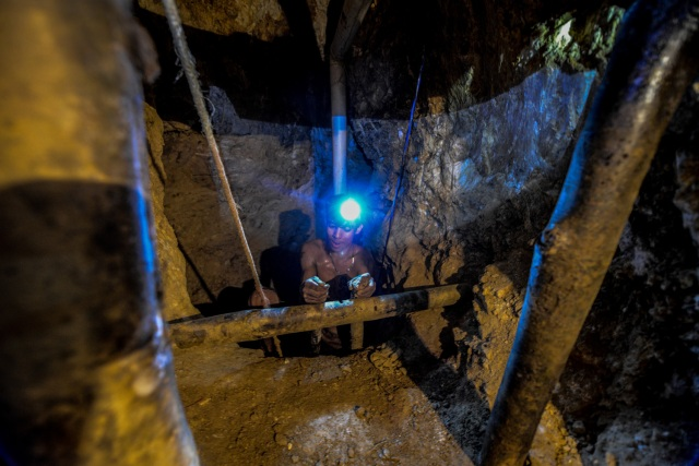 Ender Moreno descends looking for gold at La Culebra gold mine in El Callao, Bolivar state, southeastern Venezuela on March 1, 2017. Although life in the mines of eastern Venezuela is hard and dangerous, tens of thousands from all over the country head for the mines daily in overcrowded trucks, pushed by the rise in gold prices and by the severe economic crisis affecting the country, aggravated recently by the drop in oil prices. / AFP PHOTO / JUAN BARRETO / TO GO WITH AFP STORY by Maria Isabel SANCHEZ