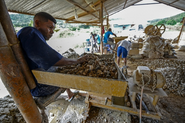 A man works at a stone crusher machine in a gold mine in El Callao, Bolivar state, southeastern Venezuela on February 25, 2017. Although life in the mines of eastern Venezuela is hard and dangerous, tens of thousands from all over the country head for the mines daily in overcrowded trucks, pushed by the rise in gold prices and by the severe economic crisis affecting the country, aggravated recently by the drop in oil prices. / AFP PHOTO / JUAN BARRETO / TO GO WITH AFP STORY by Maria Isabel SANCHEZ