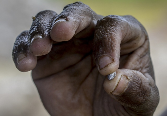 Jorge Sanchez, 24, shows a gold-mercury amalgam at a gold mine in El Callao, Bolivar state, southeastern Venezuela on February 25, 2017. Although life in the mines of eastern Venezuela is hard and dangerous, tens of thousands from all over the country head for the mines daily in overcrowded trucks, pushed by the rise in gold prices and by the severe economic crisis affecting the country, aggravated recently by the drop in oil prices. / AFP PHOTO / JUAN BARRETO
