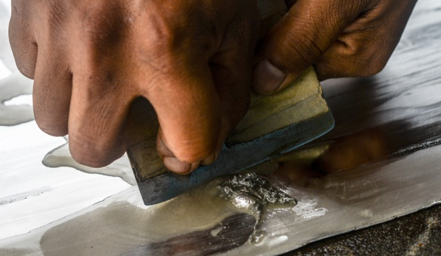 A worker scrapes gold-mercury amalgam from an aluminium sheet at a gold mine in El Callao, Bolivar state, southeastern Venezuela on February 25, 2017. Although life in the mines of eastern Venezuela is hard and dangerous, tens of thousands from all over the country head for the mines daily in overcrowded trucks, pushed by the rise in gold prices and by the severe economic crisis affecting the country, aggravated recently by the drop in oil prices. / AFP PHOTO / JUAN BARRETO / TO GO WITH AFP STORY by Maria Isabel SANCHEZ