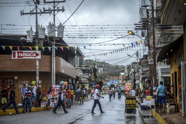 "View of a sign reading ""We buy gold"" in a street of El Callao, Bolivar state, southeastern Venezuela on February 25, 2017. Although life in the mines of eastern Venezuela is hard and dangerous, tens of thousands from all over the country head for the mines daily in overcrowded trucks, pushed by the rise in gold prices and by the severe economic crisis affecting the country, aggravated recently by the drop in oil prices. / AFP PHOTO / JUAN BARRETO"
