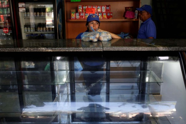 A saleswoman holds bags of bread as she waits for customers at bakery in Caracas, Venezuela March 17, 2017. REUTERS/Marco Bello