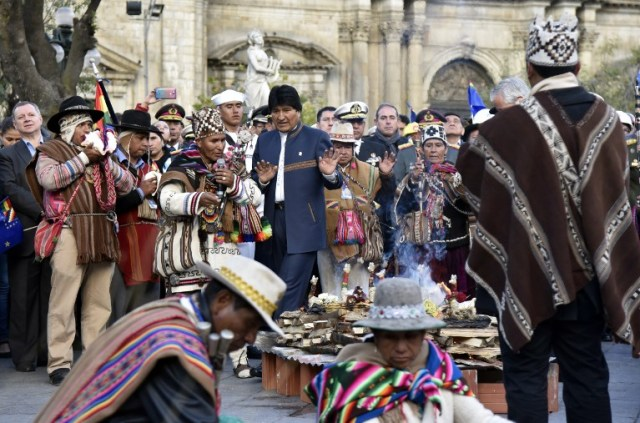 Bolivian President Evo Morales (C) participates in Andean rituals performed at a square in La Paz on March 21, 2017 as Morales's government submitted its response to a counter-suit filed by Chile at the International Court of Justice (ICJ), the latest legal wrangling in landlocked Bolivia's long-standing struggle to regain access to the Pacific Ocean. The two countries, currently locked in a bitter border dispute at the ICJ, severed diplomatic ties in 1978 and have a beef dating back to the War of the Pacific in the 19th century, when Bolivia lost its access to the sea to Chile. / AFP PHOTO / Aizar RALDES