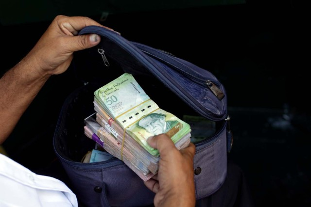 A man places banknotes in a pouch after withdrawing them from a bank branch in Caracas, Venezuela March 21, 2017. REUTERS/Marco Bello