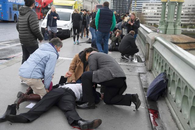 """Unas personas heridas reciben asistencia tras un incidente en el puente de Westminster en Londres, mar 22, 2017. Un policía fue apuñalado, un atacante fue abatido a tiros y varias personas resultaron heridas el miércoles cerca del Parlamento en Londres, en un suceso que está siendo tratado como un """"incidente terrorista"""" por la policía. REUTERS/Toby Melville"""